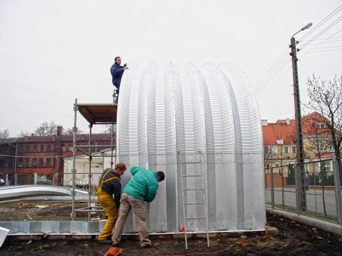 Prefabrykowane, stalowe hale łukowe - kolejne montowane przęsła hali łukowej są dokręcane do zmontowanych łuków.