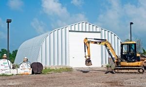 Samonośne hale łukowe - prefabrykowana hala łukowa jako łukowy garaż na maszyny budowlane. Łuki mają proste, nachylone ściany.
