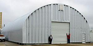 Stalowe hale łukowe - hala łukowa C o pionowych ściana i łukowym dachu zastosowana jako magazyn przemysłowy.