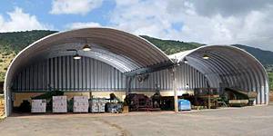 Prefabrykowane, stalowe hale łukowe - wielonawowa samonośna hala łukowa z dachem łukowym, zastosowana jako magazyn.