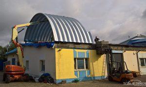 Samonośne hale łukowe - prefabrykowana stalowa hala łukowa jako lekki łukowy dach podczas montażu na istniejącym dachu płaskim.