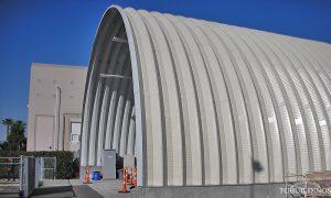 Samonośne hale łukowe - hala łukowa jako prefabrykowana wiata na murowanej ściance kolankowej. Łuki w kolorze - jasny szarobrązowy (lightstone).