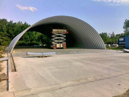 Samonośne hale łukowe - prefabrykowana stalowa hala łukowa - montaż bez konektorów (łączników montażowych) w korytku w betonowej płycie fundamentowej.