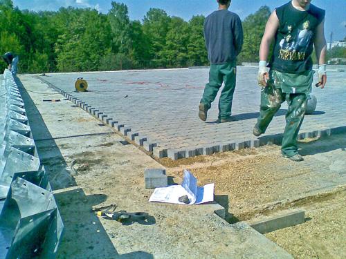 Samonośne hale łukowe - prefabrykowana stalowa hala łukowa - montaż za pomocą konektorów na płytach drogowych z wypełnieniem podłogi kostką brukową.