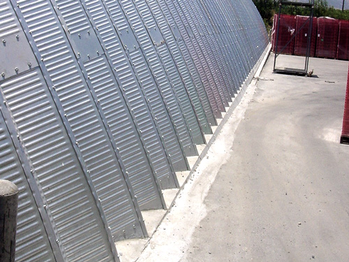 Samonośne hale łukowe - prefabrykowana stalowa hala łukowa - montaż z uszczelnieniem łuków betonem.
